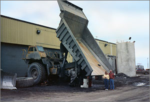 Photo of a man and woman standing near a large dump truck.