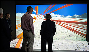 In this photo, two men are facing a giant screen that shows ribbons of yellow and orange against a white background. A white wind turbine blade can be seen in the background.