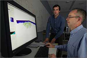 In this photo, two scientists look at a computer screen that features green diagonal lines coming from a blue background.