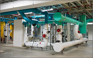 This is a photo of large-diameter green, blue, and white pipes arranged horizontally from just above the floor to just below the ceiling of what looks like a basement.