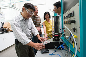 Photo of three men and one woman looking at instruments in a laboratory.
