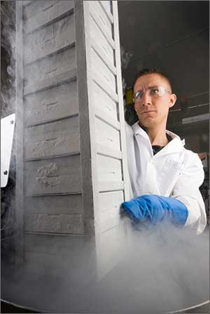 Photo of a scientist in a white lab coat in front of a tall stack of white boxes.