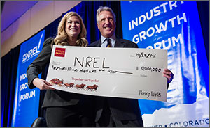 Photo of a woman and a man smiling and holding an oversized check addressed to NREL for $10 million.