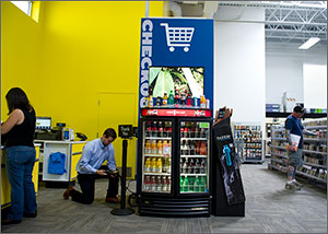 Photo of a man on one knee looking at a portable monitor that is plugged into a chilled display of soft drinks and juices. In the background, a customer at Best Buy peruses merchandise.
