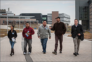 Photo shows a woman and four men walking through NREL's campus on a chilly day, with laboratory buildings in the background.