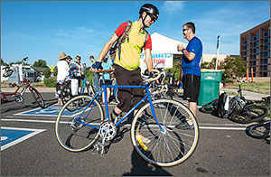 Photo of a man in a bicycle helmet walking his blue road bike past a tent that is serving as a breakfast location for bicyclists at Bike to Work Day at NREL.