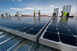 Photo of men in safety gear working to install PV modules on a rooftop.