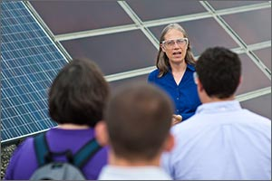 Photo of NREL's Sarah Kurtz speaking to a gathering of people with solar modules in the background.