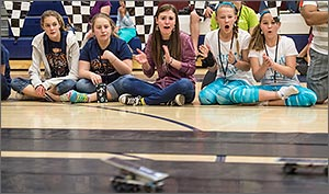 Photo of a group of students watching a race between solar-powered cars.