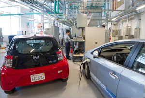 Photo of a researcher working in a laboratory with two electric vehicles and various power equipment.