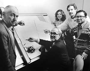 Black and white photo of a group gathered around a drawing board.