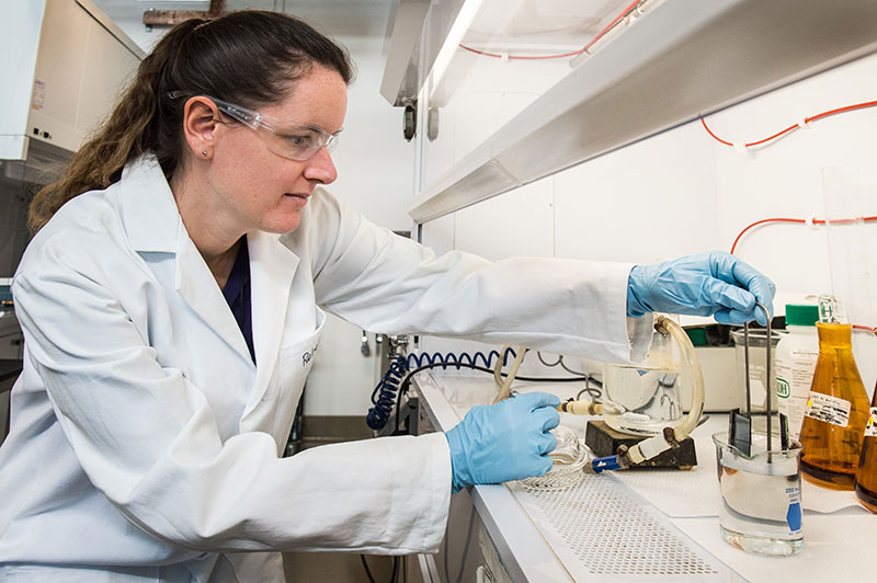 A woman in a lab coat works with instruments in a laboratory.