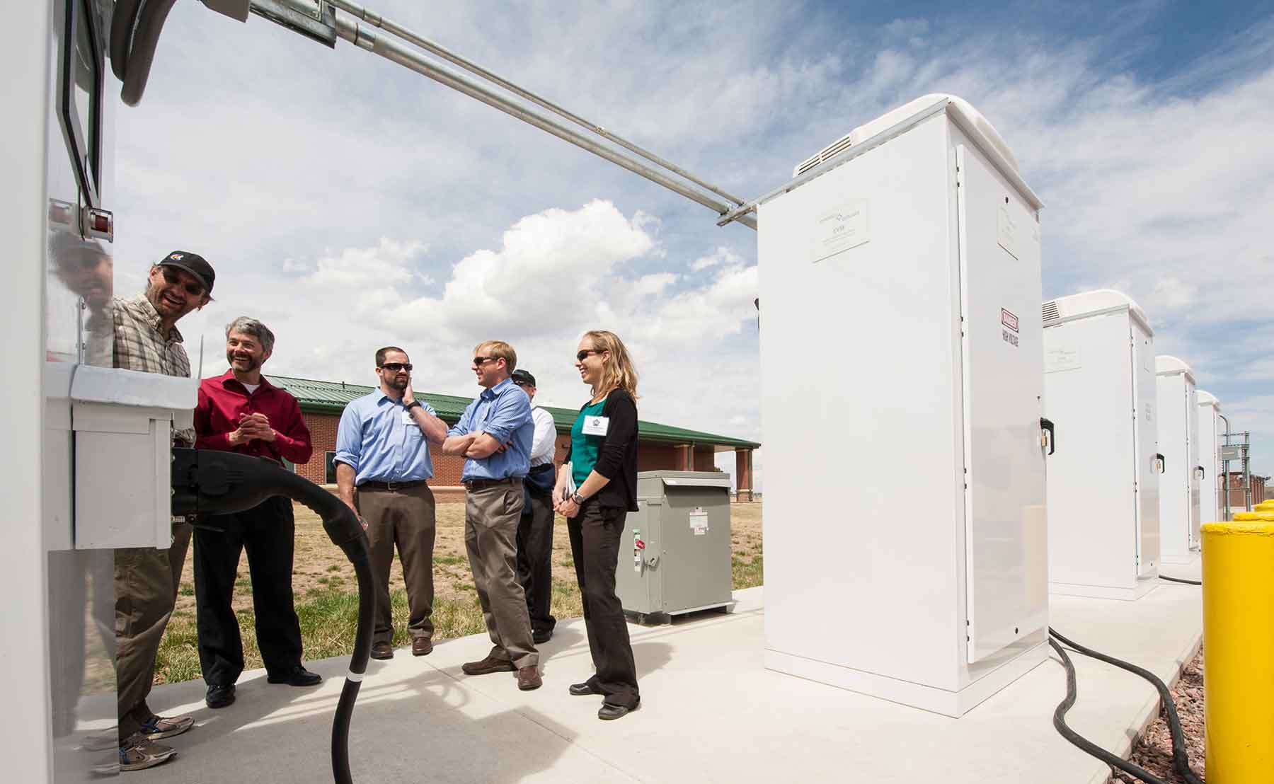 A group of researchers from NREL examines a piece of equipment at an Army base.