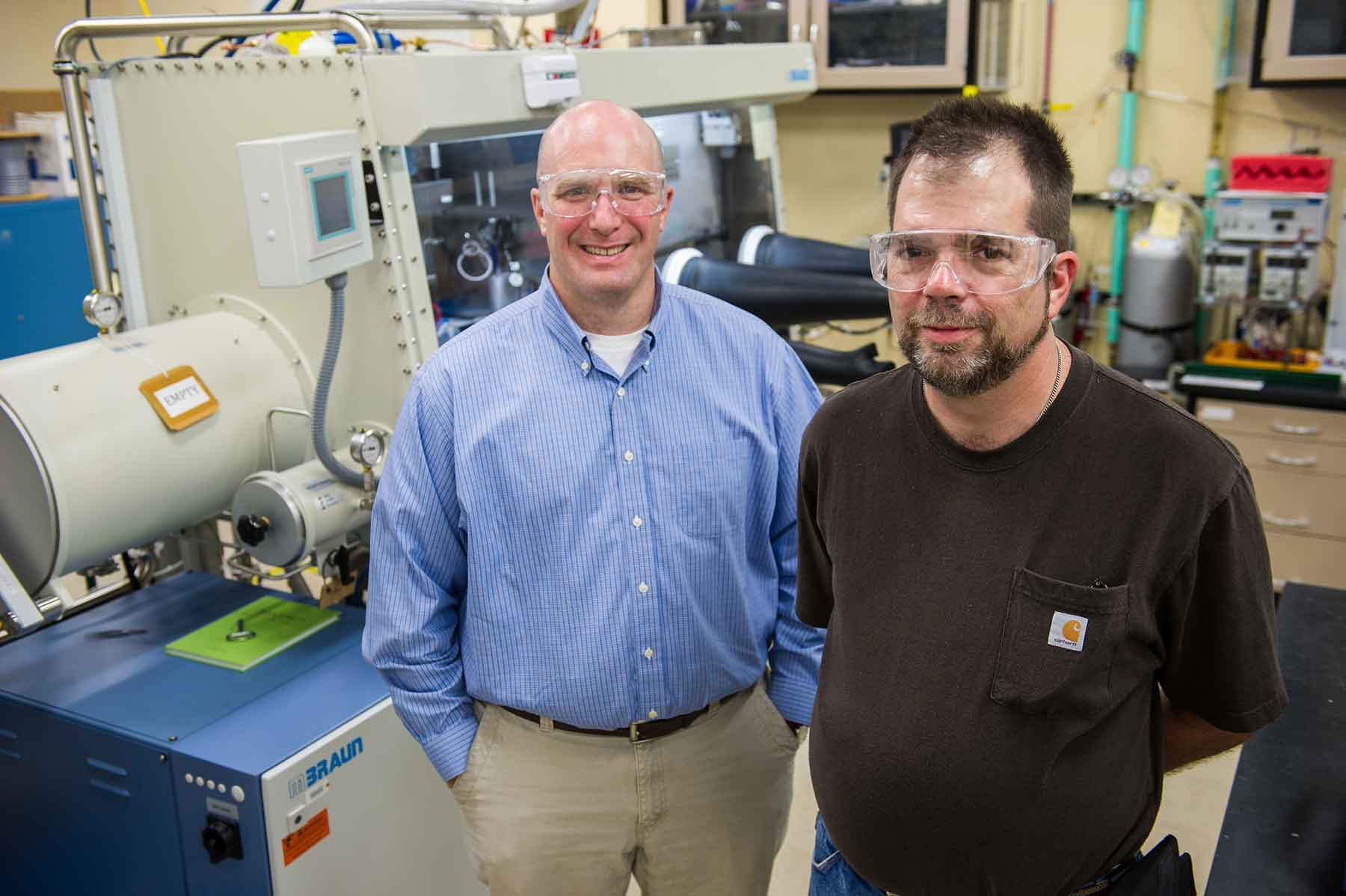 Two NREL researchers stand in a lab.