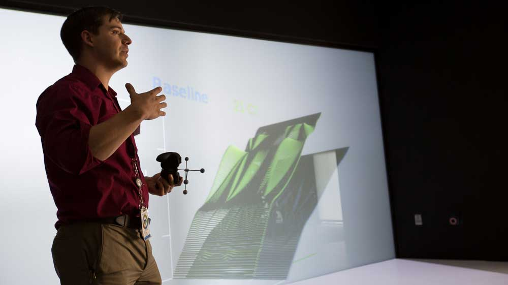 Photo of a man standing in front of a 3-D screen.