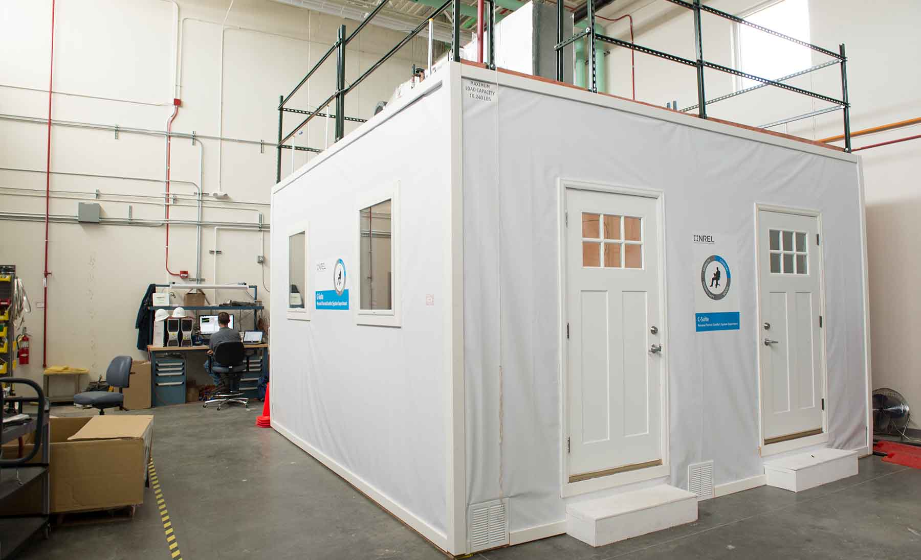 Photo shows the Comfort Suite structure, a white room with two doors and windows in a laboratory facility.