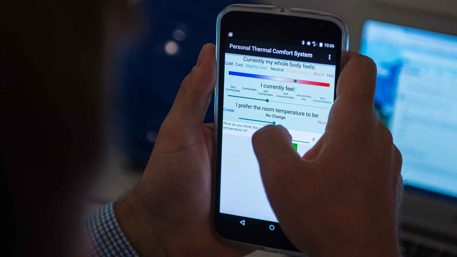 Photo shows a man using a smartphone app to register his comfort level.
