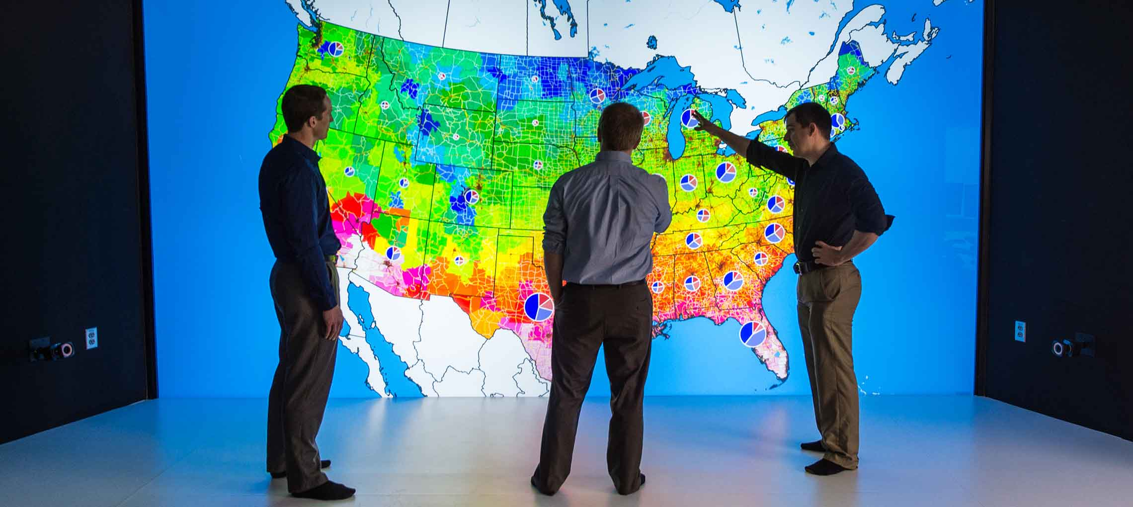 NREL researchers look at colored map of the United States in 3D visualization room.