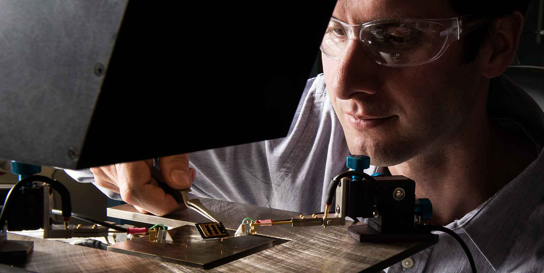 Photo shows a researcher positioning a solar cell he developed on a solar simulator.