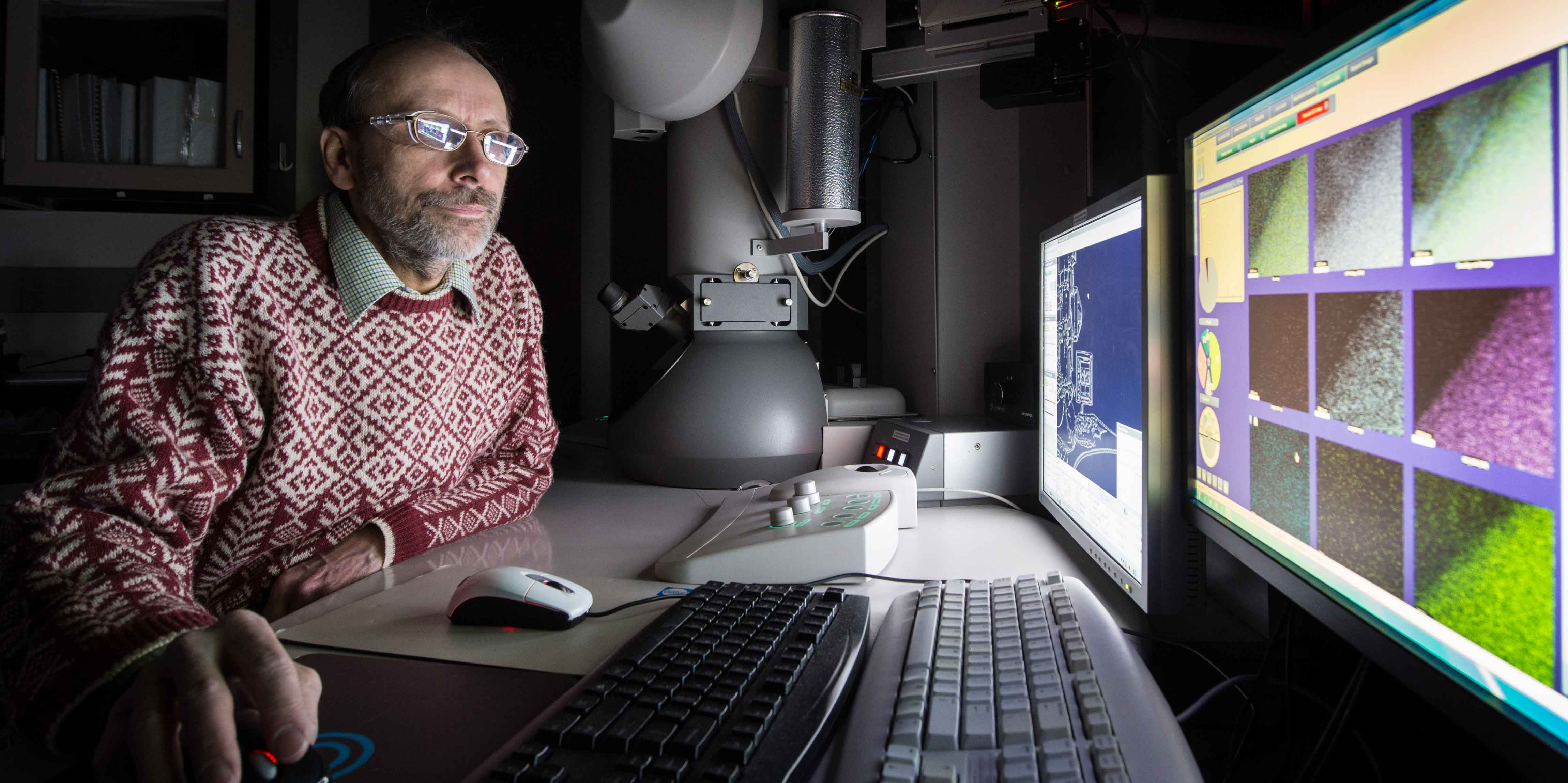 A man looks at images through a scanning transmission electronic microscope.