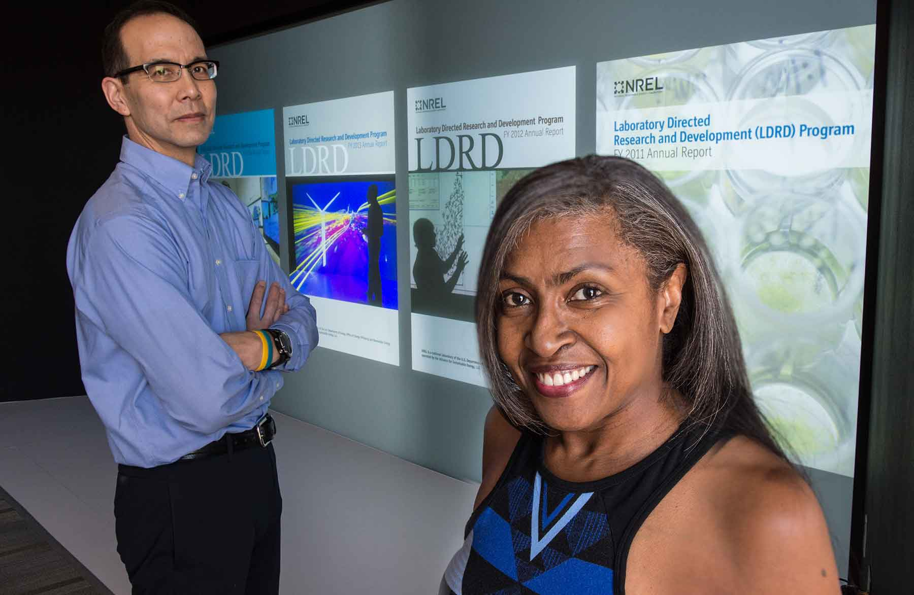 Two people stand in front of a screen displaying reports about NREL's LDRD program.