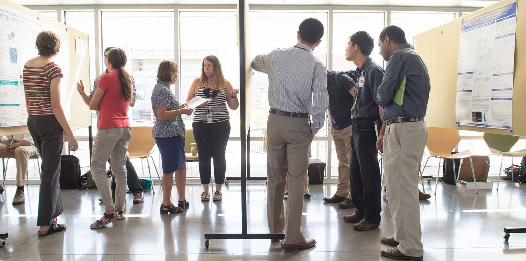 A group of people examine posters displaying results of LDRD-funded research.
