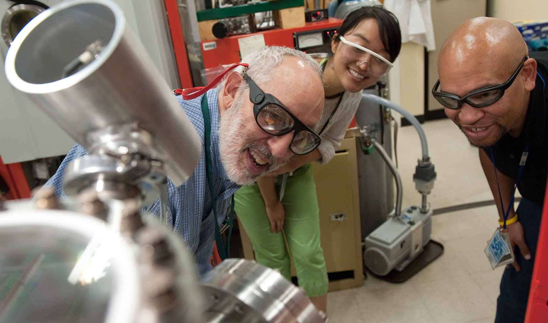 Two men and a woman in goggles look at a piece of lab equipment.