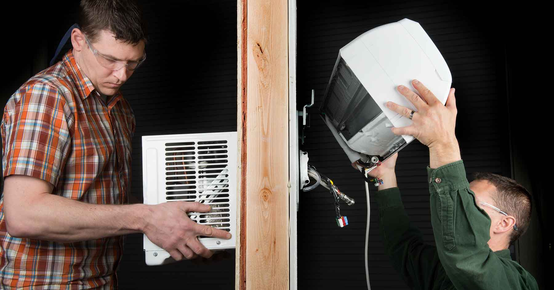 two men shown on opposite sides of a wall installing the ecosnapac heat pump