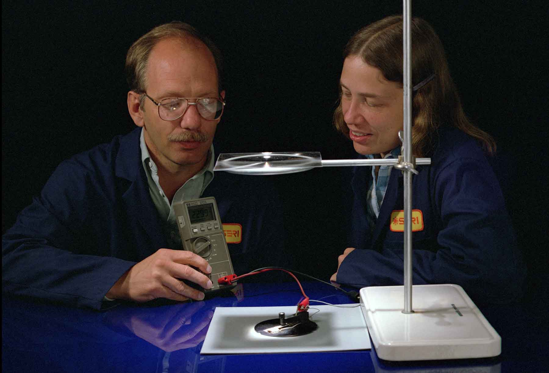 A man and a woman look at a solar cell.
