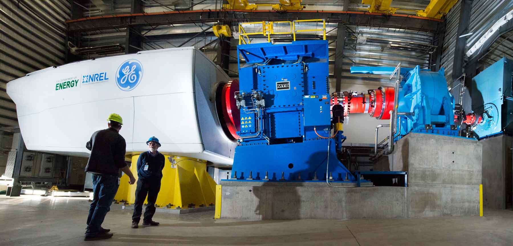 Two men in hardhats and safety glasses stand in front of equipment having a conversation. The blue and white dynamometer equipment has a white wind turbine drivetrain attached to it for testing.