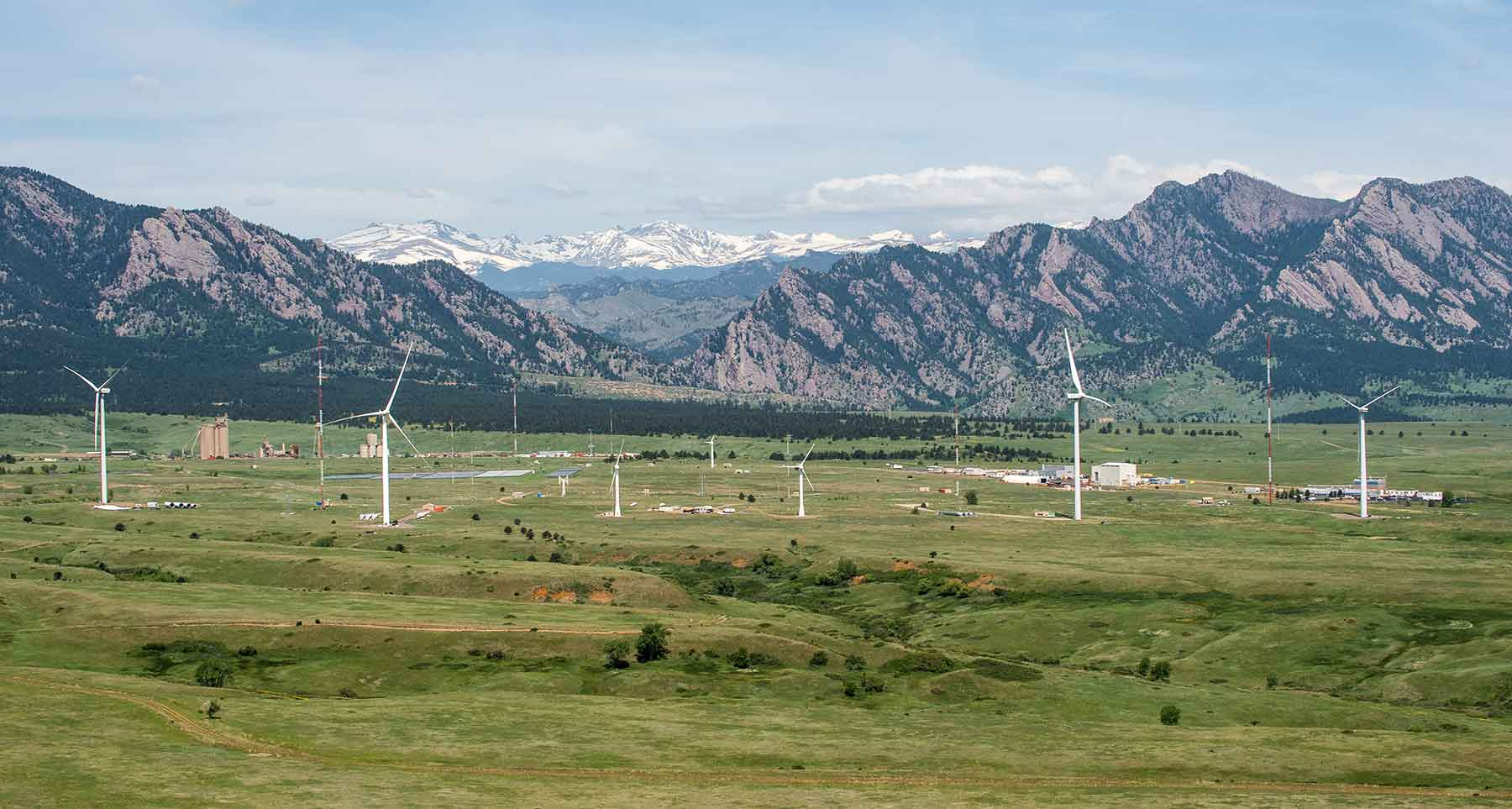 A wide aerial view of a wind turbine testing site and the landscape surrounding it. One large wind turbine is in the foreground with four other wind turbines behind it, as well as several buildings and met towers. Mountains are in the background