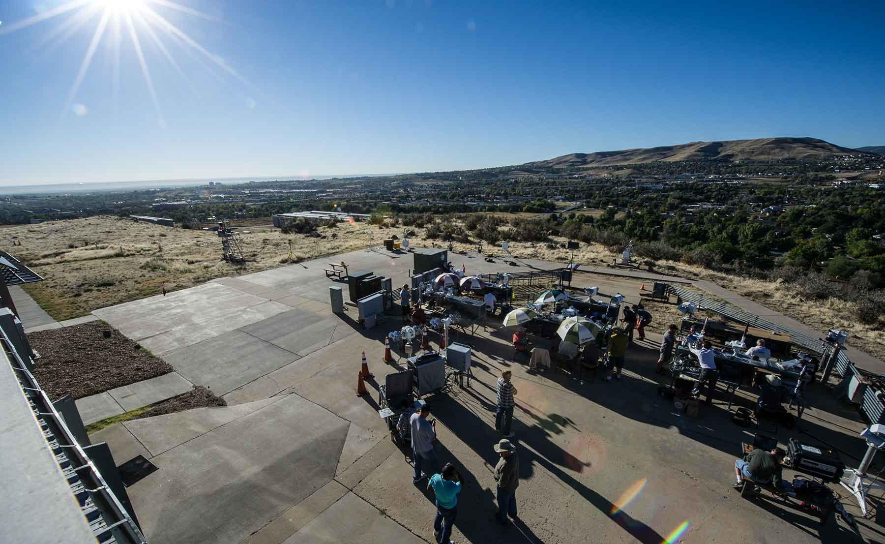 Several dozen people work outside with solar radiation instruments on a mesa.