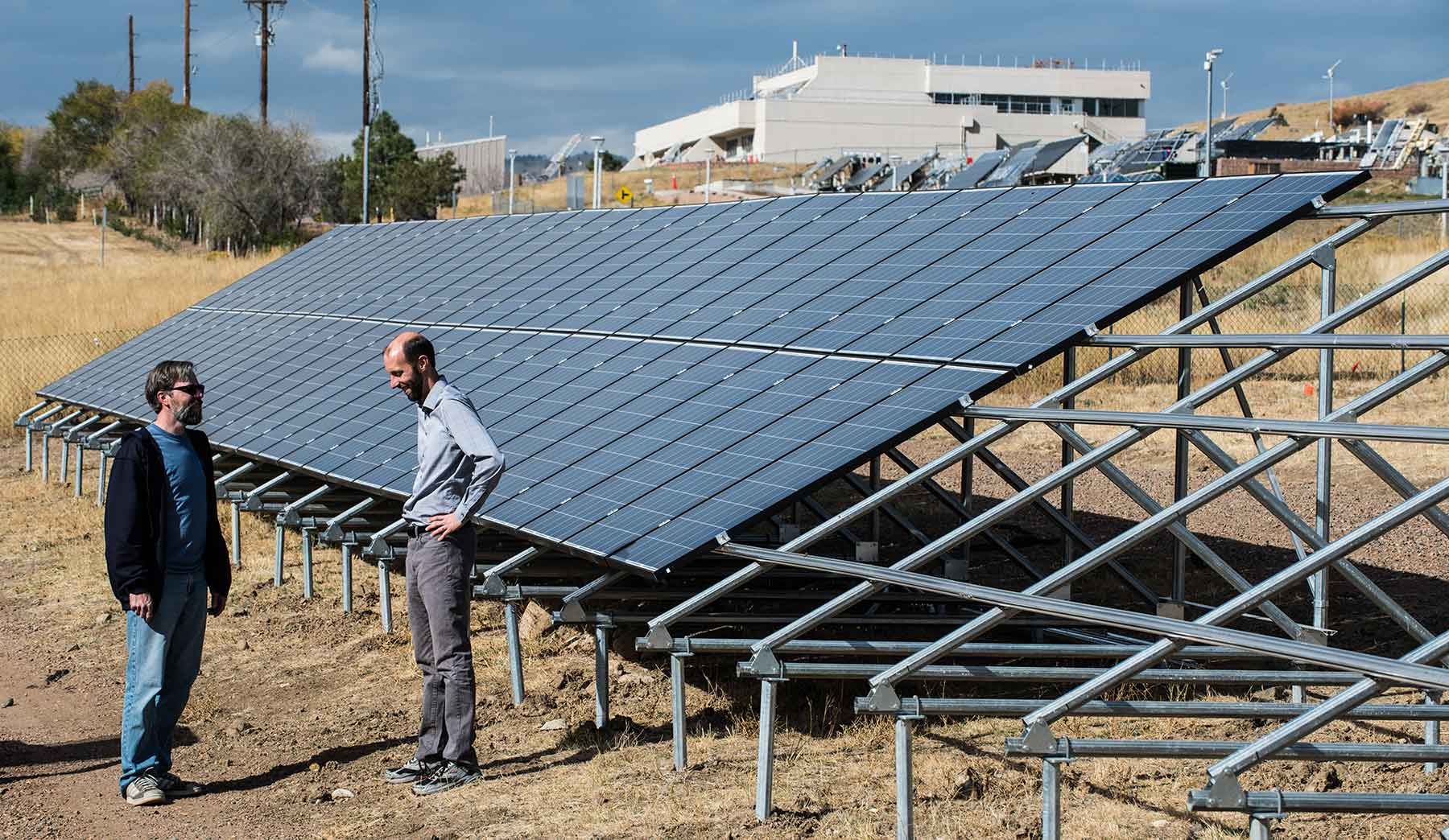 Two men stand next to solar modules in a field on the NREL campus.