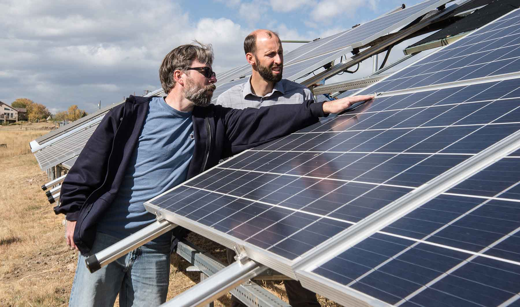 Two men examine solar modules set up in a field on the NREL campus.