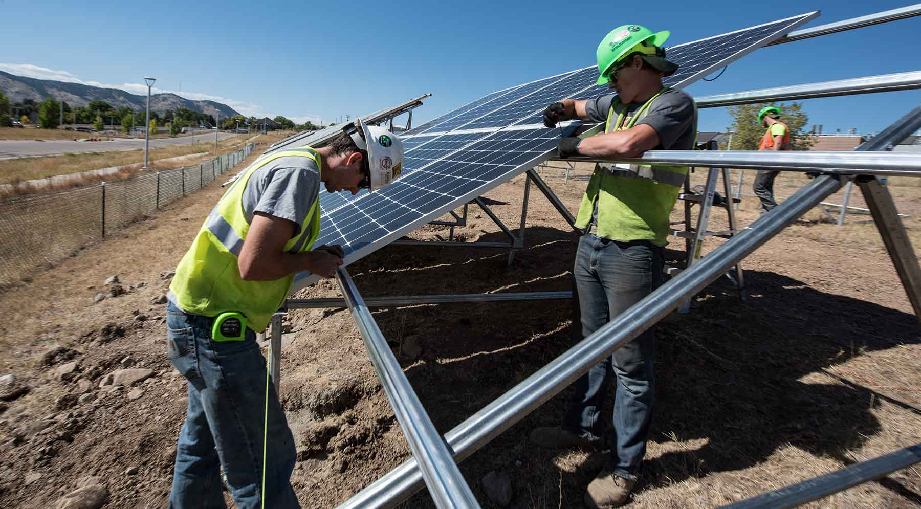Workers install PV modules at NREL's new solar array field.