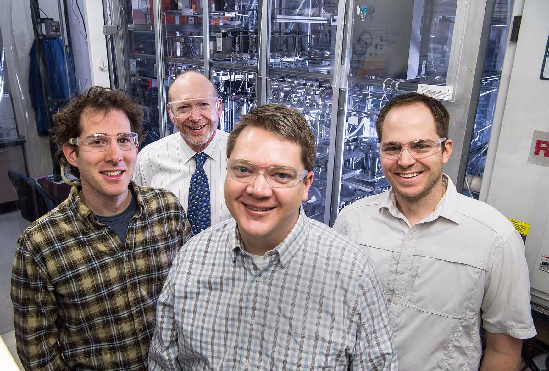 Four men stand in front of a device used to grow crystalline semiconductor structures.