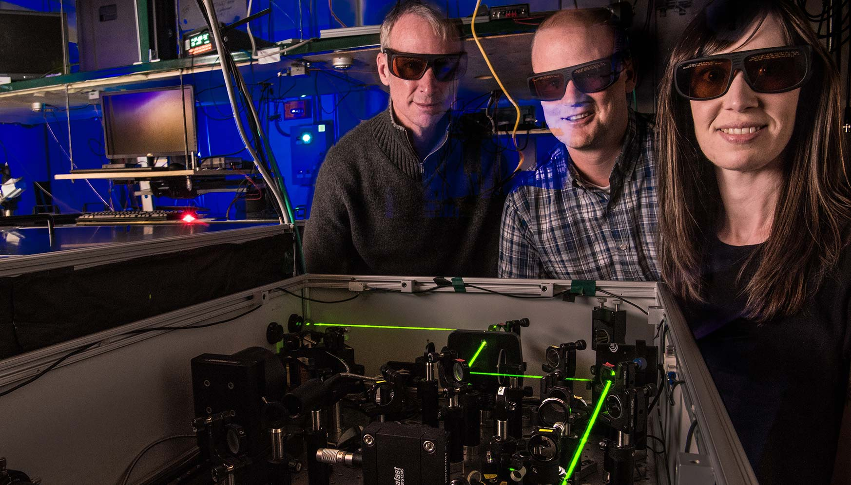 Two men and one woman wearing dark glasses stand next to a laser.