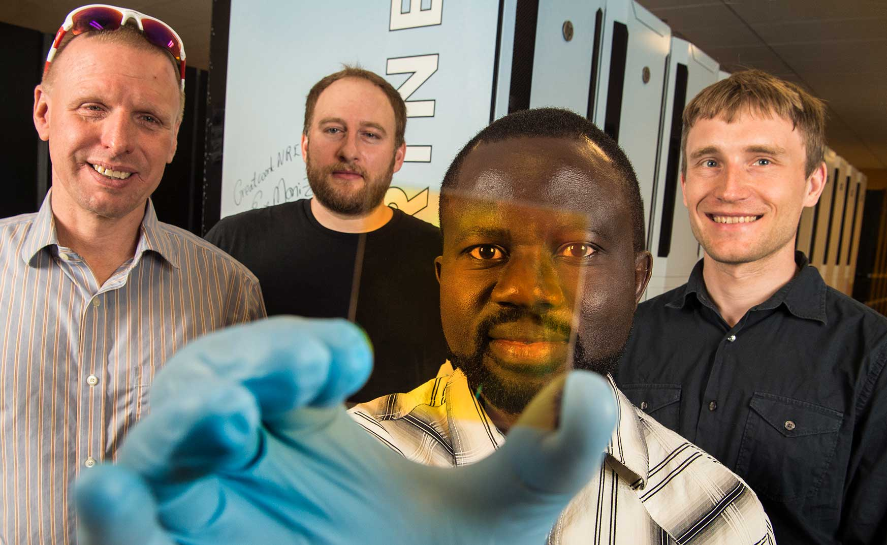 NREL team holds up new alloy sample that may become part of the next-generation semiconductors.