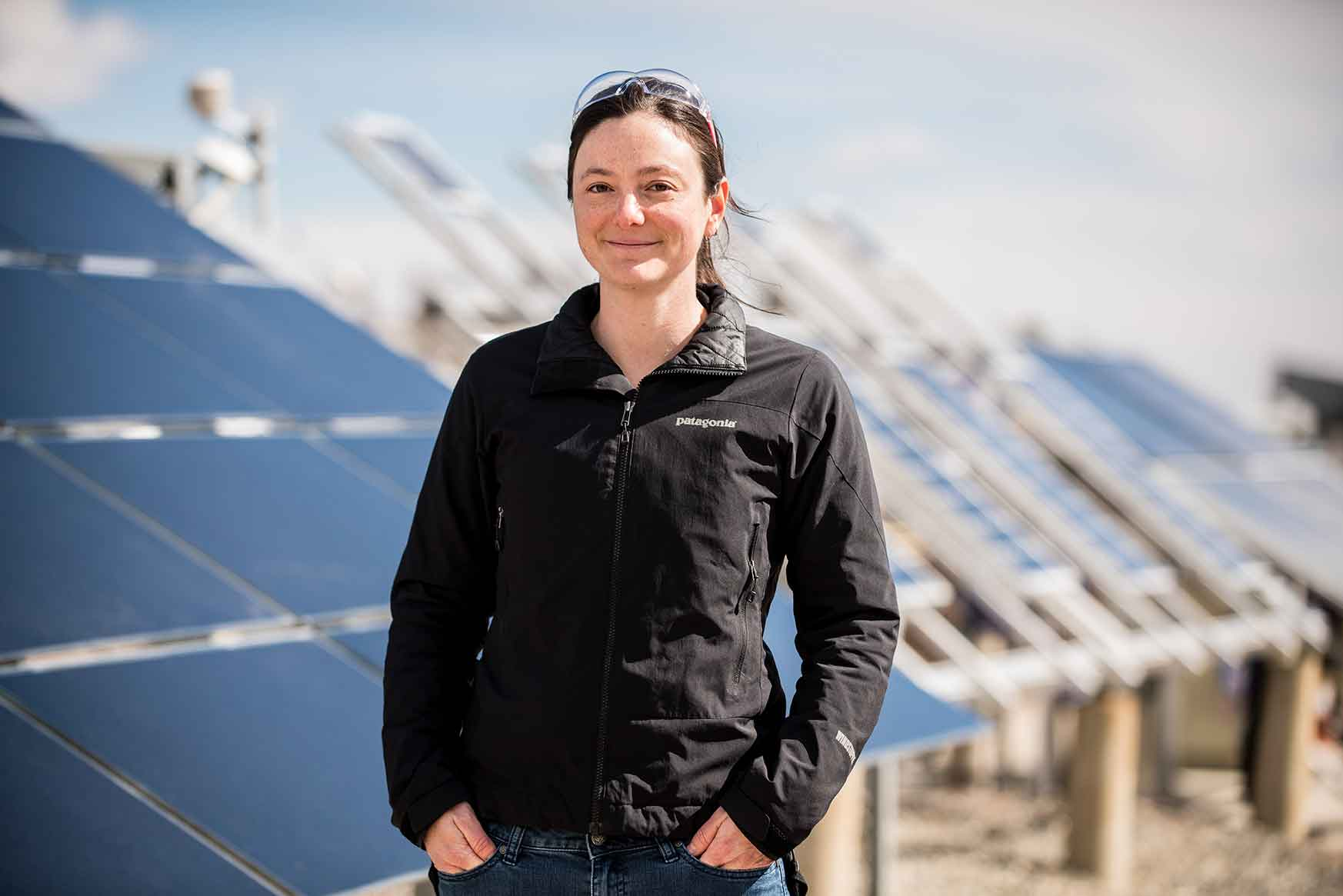 A woman stands in front of solar panels.