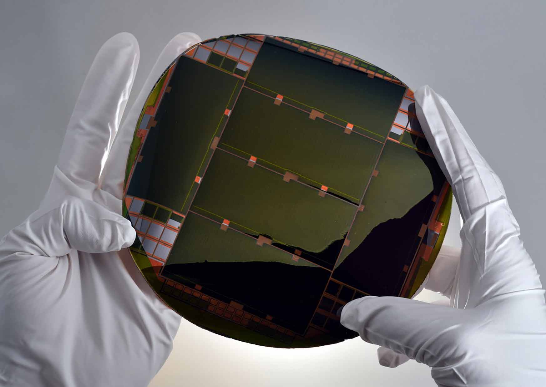 Two hands holding the IMM solar cell
