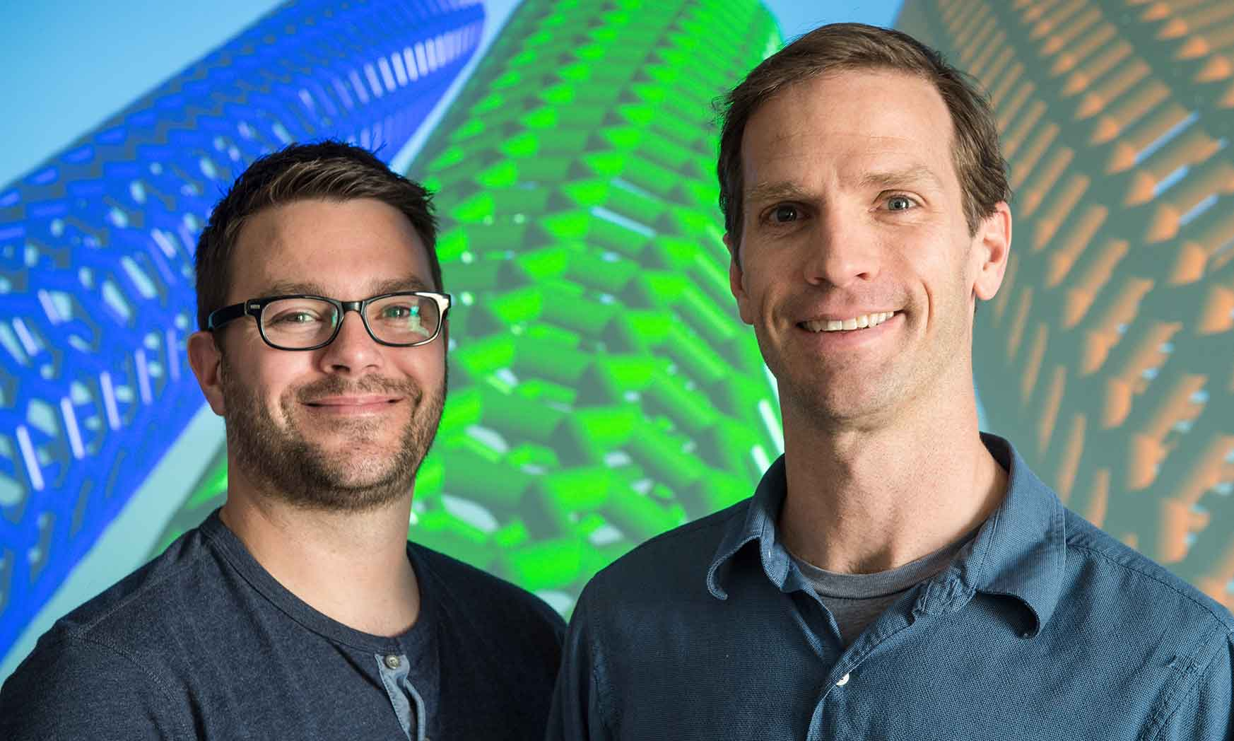 Two men stand in front of a screen that shows carbon nanotubes.
