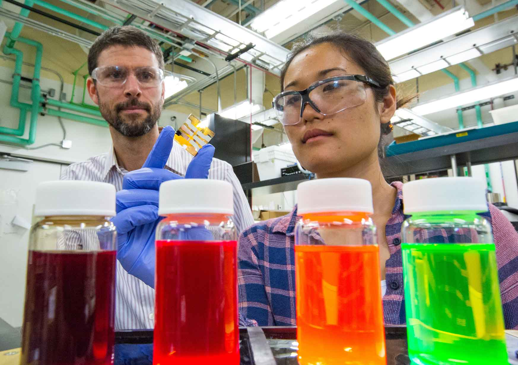 A woman holds a small thin film while a man looks on. (Photo by Werner Slocum / NREL)