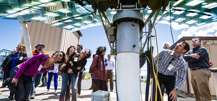 People look up at a piece of solar equipment.