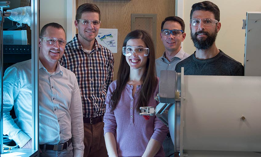 Four men and a woman stand inside a research laboratory at NREL.