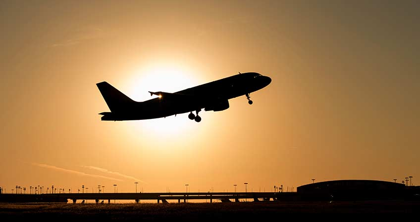An airplane takes off at Dallas Fort Worth International Airport at sunset.