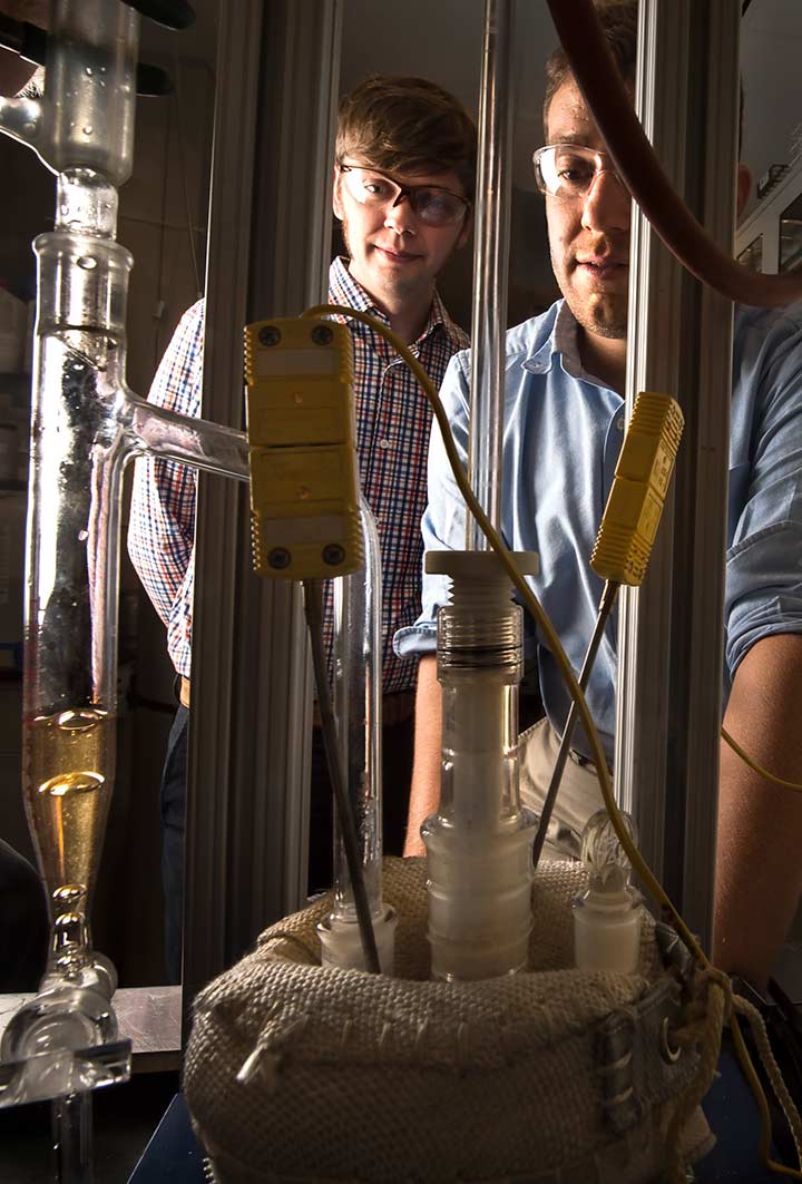 Two scientists look at glass flasks and tubes in a laboratory.