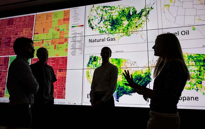 Four NREL researchers working on the ResStock building analysis tool discuss their work in front of a large visualization screen.