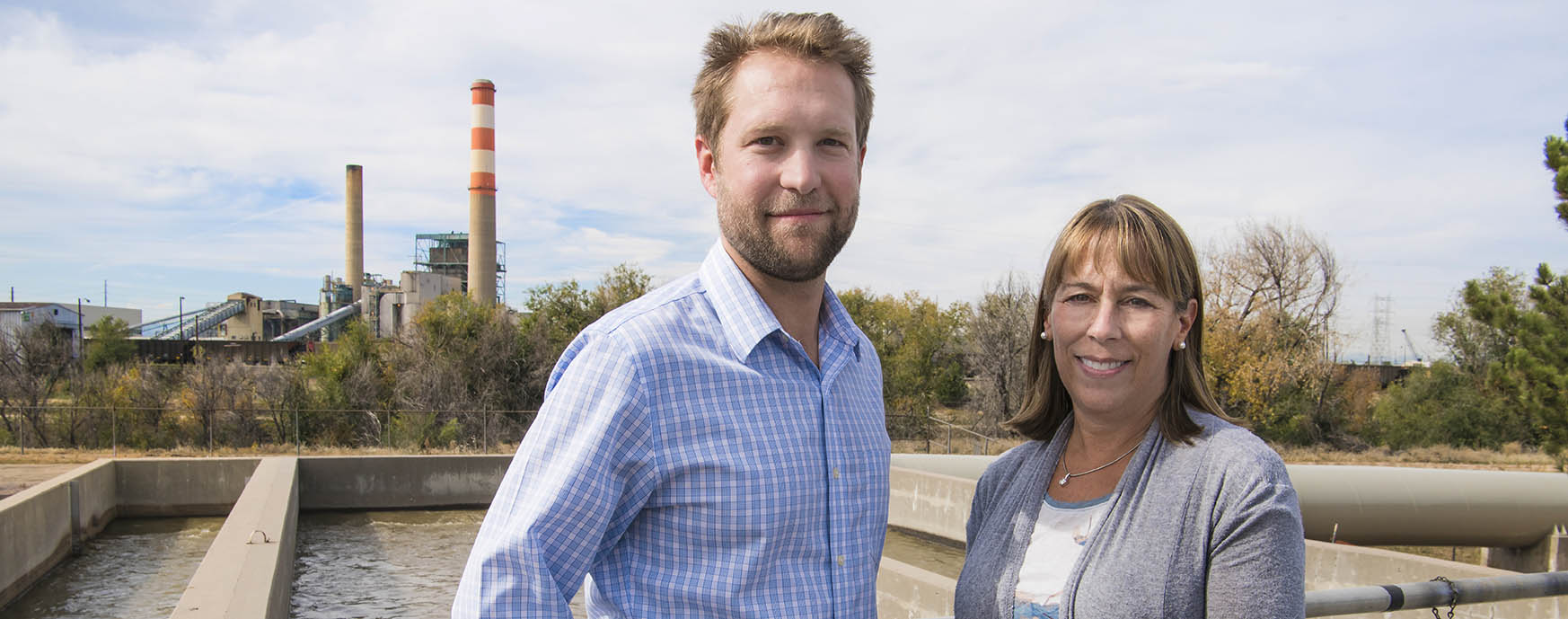 Photo of man and woman standing outside with power plant in background.