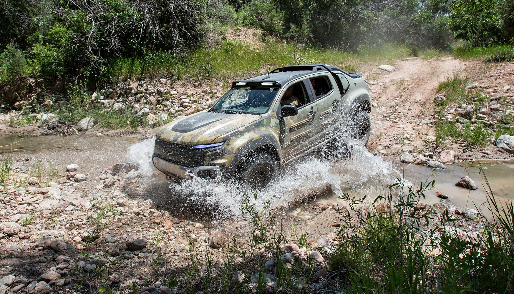 The GM Chevy Colorado ZH2 drives through a stream on the Fort Carson Army Base.