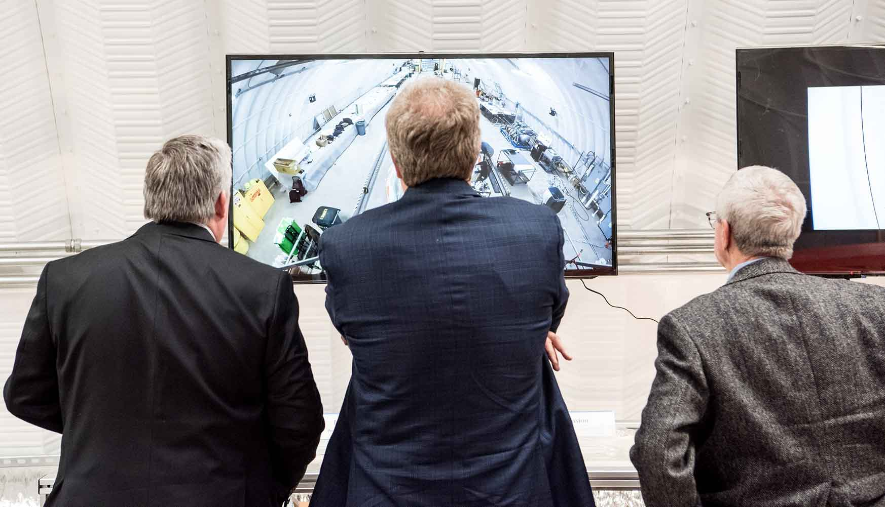 A photo of three men watching a television screen showing a time lapse video of the construction of a wind turbine blade.